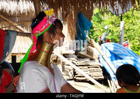 Baidjan KAREN VILLAGE, THAÏLANDE - 17 décembre. 2017: de vieux long cou femme assise en face d'une cabane en bambou avec un toit de chaume Banque D'Images