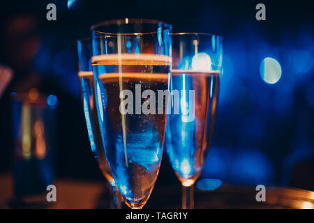 Lunettes avec champagne dans une lumière colorée à l'occasion d'une fête Banque D'Images