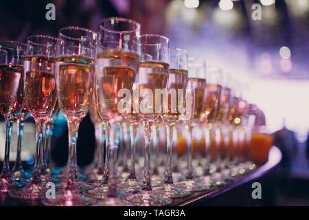 Lunettes avec champagne dans un multi-colored light party Banque D'Images