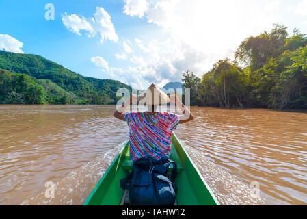 Femme avec coiffe traditionnelle croisière sur l'eau brune de la rivière Nam Ou au Laos, un paysage extraordinaire jungle montagne célèbre destination touristique dans sou