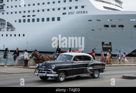 La Havane, Cuba - 1950 American voiture conduit au-delà d'un chariot et d'un navire de croisière sur l'Avenida del Puerto près de le port de La Havane. Voitures américaines classiques f