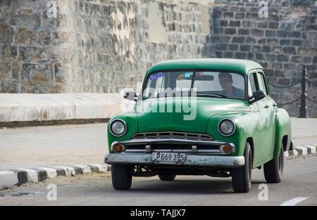 La Havane, Cuba - Un taxi passe devant Castillo de San Salvador de la Punta Sur le Malecón road face à la baie de La Havane. Voitures américaines classiques du 19 Banque D'Images