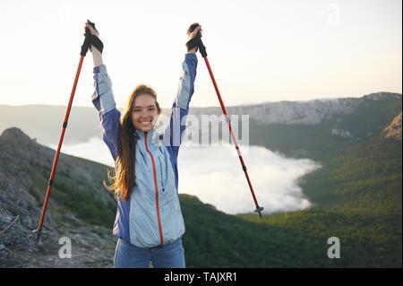 Heureux et souriant belle femme randonneur se tient dans les montagnes avec les bâtons de trekking et garde ses mains. Le concept de la randonnée en montagne Banque D'Images