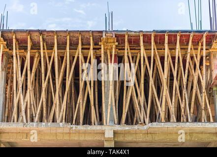 La construction en Inde. Un échafaudage de bambou utilisé pour appuyer un nouveau béton de ciment coulé (RCC) dalle du toit. Banque D'Images