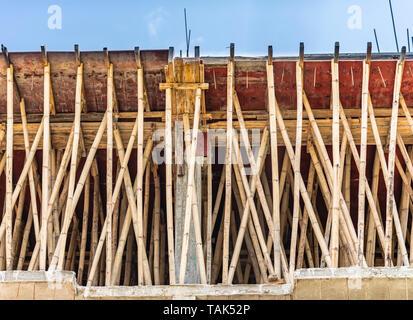 Un échafaudage de bambou utilisé pour soutenir un toit en béton de ciment renforcé de la dalle. Le nouveau toit est coulé à gauche de remède pour environ 7 jours. L'Inde. Banque D'Images