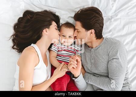 Mère et père embrassant leurs bébé adorable Banque D'Images