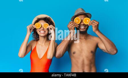 Cheerful young couple holding deux moitiés d'orange près de yeux Banque D'Images