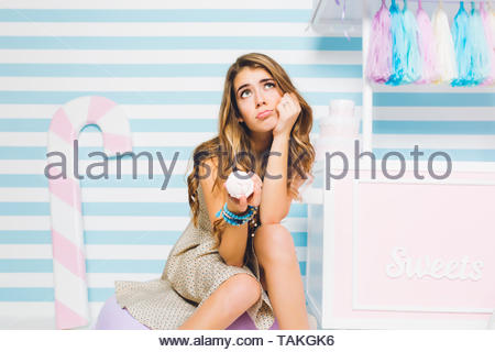 Dreamy brunette girl doute qu'il est bon de manger la crème glacée refroidissement sur mur à rayures. Portrait d'une jeune femme assise à côté de sweets shop et tenant dans la main. dessert savoureux Banque D'Images