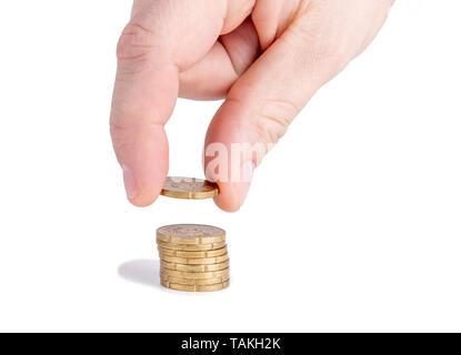 La main de l'homme mettre de l'argent à pile de pièces. Banque D'Images
