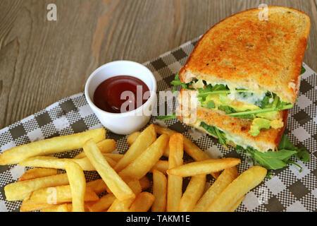 Salade d'avocat au poulet sandwich et frites servi sur table en bois Banque D'Images