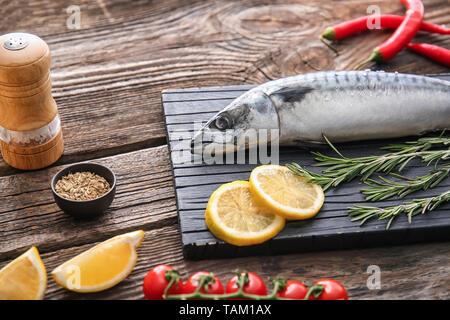 Sélection de délicieux plats de poisson maquereau cru, citron et romarin sur table en bois Banque D'Images