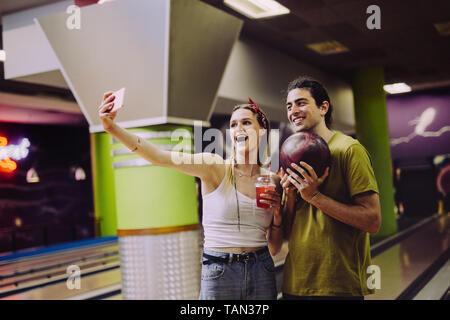 Couple qui à selfies bowling. Femme tenant une prise de boisson avec selfies homme tenant une boule. Banque D'Images