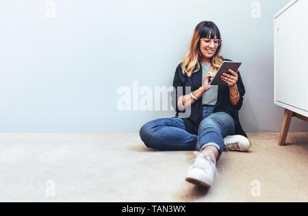 Smiling woman sitting on floor using a tablet pc. Contrôle de ses mails businesswoman détendue sur un tablet pc.