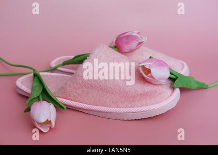 Chaussons rose sur un fond rose. A proximité, fleurs roses. Accueil terry chaussons et des tulipes sur fond rose. Banque D'Images
