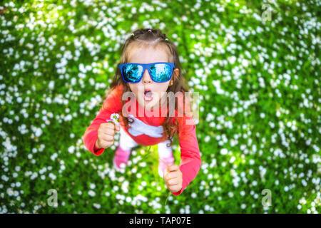 Happy smiling petite fille aux cheveux bouclés parmi la marguerite domaine.