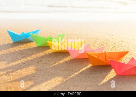 Du papier de couleur sur les rangs des bateaux de sable en plein air au coucher du soleil. Selective focus sur l'avant Banque D'Images