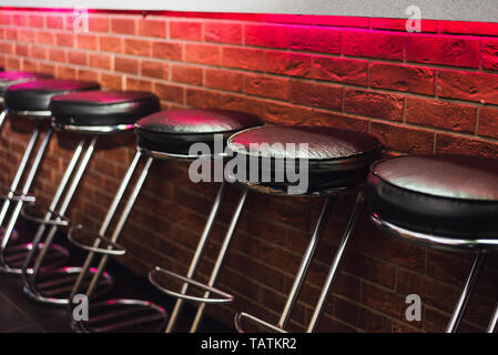 Tabourets de bar au comptoir dans neon light. chaise en cuir au bar Banque D'Images