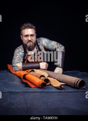 Homme à travailler avec le cuir dans son lieu de travail. Banque D'Images