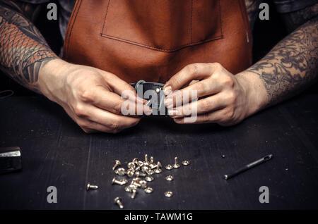 Travailleur de cuir en cuir de coupe présente pour sa nouvelle production dans son atelier. Banque D'Images