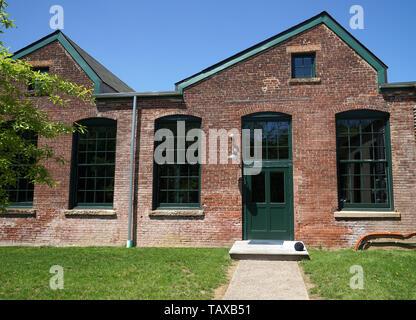 Extérieur d'un ancien moulin à soie a la façade en brique rouge, portes industrielles et portes vieux vert. Banque D'Images
