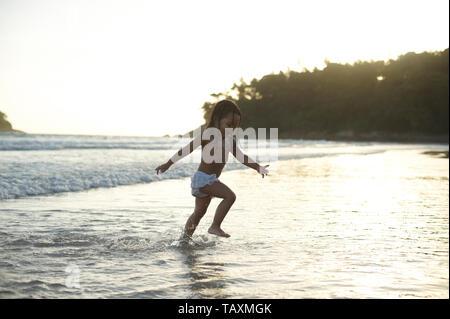 Amazing shot d'une mignonne petite fille asiatique s'exécutant dans l'eau peu profonde le long de la plage en Thaïlande s'amusant aux prises avec quelque chose de nouveau dans sa vie Banque D'Images