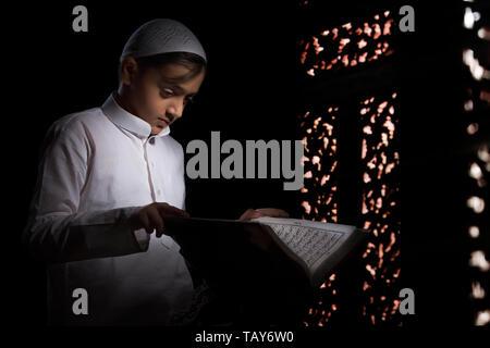 Garçon musulman Coran lecture Banque D'Images