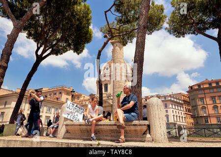 Rome, Italie - très jeune fille assise à une grève contre le changement climatique tout en ayant un sandwich. Son père est boire d'une bouteille en plastique Banque D'Images