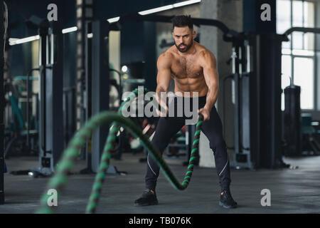 Homme travaillant sur de remise en forme avec salle de sport de combat à cordes Banque D'Images