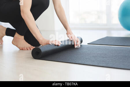 Portrait of female hands rolling tapis de yoga Banque D'Images