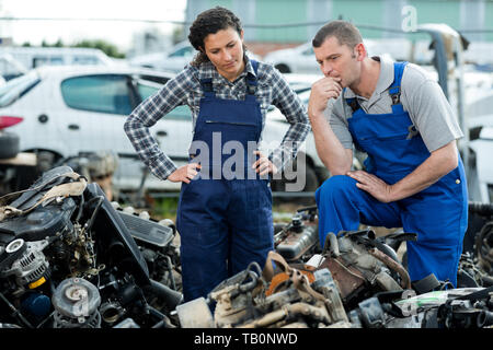 L'homme et la femme travaillant sur junkyard Banque D'Images