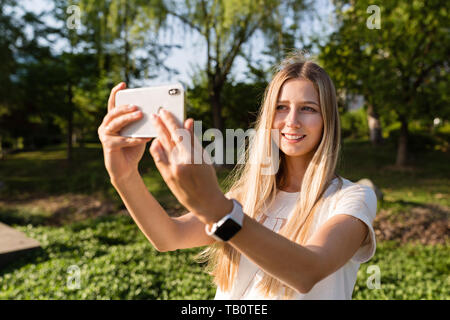 Belle jeune femme aux cheveux blonds à l'aide de téléphone mobile à l'extérieur. Girl making élégant dans le parc selfies Banque D'Images