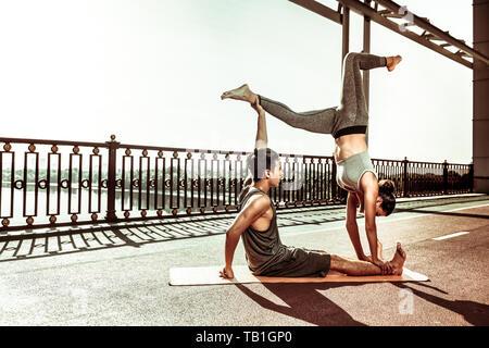 Jeune couple en bonne santé dans les vêtements de sport faire acroyoga pose Banque D'Images