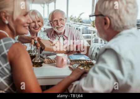 Plaisir positif d'âge mûr ayant dîner en famille Banque D'Images