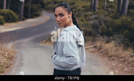 Vue arrière d'aptitude femme marche sur route de campagne et à à l'épaule. Femme sportive sur chemin.