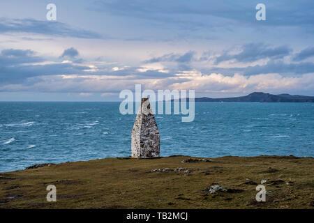 La baie de Cardigan et cairn de pierre marquant l'entrée du port de l'Pembrookeshire Porthgain Coast Trail, le Parc National de Pembrokeshire, Pays de Galles, Royaume-Uni. Banque D'Images