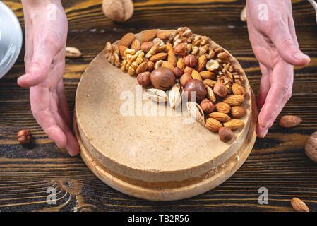 Caramel noisette gâteau au fromage avec garniture de noix, amandes, noisettes et noix macadamia sur un fond de bois sombre. L'écrou à la maison d'un dessert. Banque D'Images