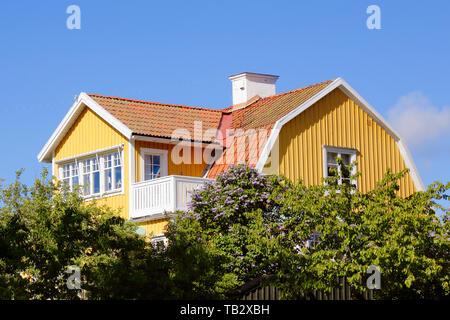 Vue extérieure d'un sol en bois de deux étages jaune 1920 maison unifamiliale en partie caché derrière des arbres dans son jardin. Banque D'Images