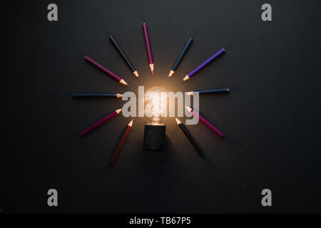 Ampoule Lumière brillant dans le noir sur noir télévision jeter avec des crayons. L'idée de l'ingénierie, la construction ou la construction concept avec copie espace. Banque D'Images
