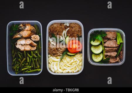 L'alimentation saine dans les conteneurs sur fond noir: collation, dîner, déjeuner. Du poisson cuit au four, des haricots, de la viande bovine escalopes, purée de pommes de terre, viande et légumes à Banque D'Images