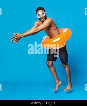L'homme torse nu noir gai dans des lunettes de natation et anneau gonflable s'amusant, plongée sous-marine sur fond bleu studio, l'espace libre Banque D'Images