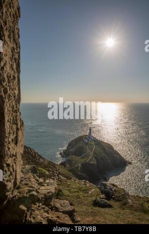 Beaux paysages gallois: phare de South Stack sur Holy Island au coucher du soleil, près de Holyhead, Anglesey, Pays de Galles, Royaume-Uni. Les rayons du soleil brillait dans l'océan. Banque D'Images