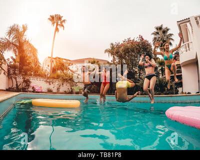Groupe d'amis heureux de sauter dans la piscine au coucher du soleil - Crazy jeunes s'amusant faisant partie de maison tropicale exclusive Banque D'Images