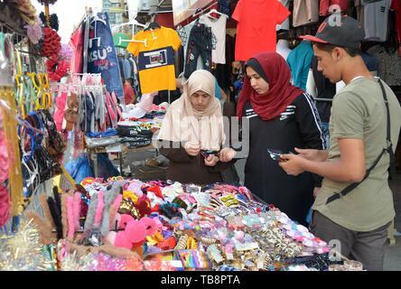 La bande de Gaza. 30 mai, 2019. Les Palestiniens à un marché de l'avant boutique de l'Eid al-Fitr dans la ville de Gaza, le 30 mai 2019. Les habitants de la bande de Gaza commencent leur tradition prépare à accueillir la prochaine l'Eid al-Fitr, la fin du mois du Ramadan. Les gazaouites utilisé pour faire du shopping dans les derniers jours du Ramadan pour acheter leurs propres vêtements, accessoires et des bonbons. Mais cette année est différente des années précédentes en raison de la conjoncture économique difficile. Pour aller avec 'caractéristique: la fête du Ramadan pas heureux à Gaza' Credit: Stringer/Xinhua/Alamy Live News Banque D'Images