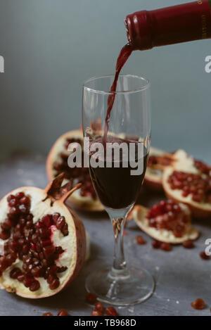 Vin rouge avec une grenade sur un fond de béton gris texturé. Un homme verse une bouteille de vin rouge dans un verre. Banque D'Images