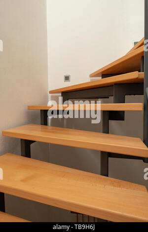 Escalier en bois design avec la construction en acier et des murs blancs dans une nouvelle maison Banque D'Images