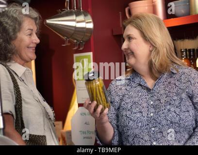 Deux femmes discutent un pot d'asperges marinées à la porte avant de Columbus, Mississippi, le 16 août 2010. Le magasin vend des aliments gastronomiques. Banque D'Images