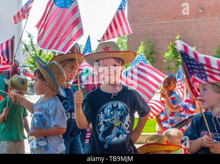 Un petit garçon est entouré par des drapeaux américains au cours d'un défilé du 4 juillet, le 30 juin 2011, à Columbus, Mississippi. Banque D'Images