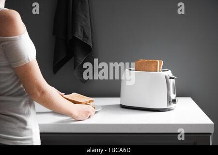 Femme porte toasts délicieux dans la cuisine Banque D'Images