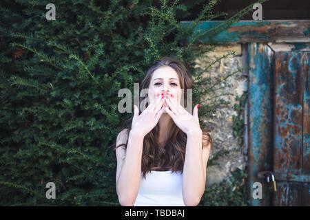 Belle fille assise près de l'abri en milieu rural, souriant et soufflant un baiser Banque D'Images