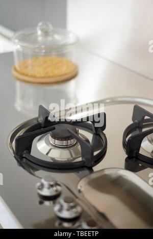 Détail d'un gaz cuisine en acier inoxydable, avec un récipient transparent rempli de céréales Banque D'Images